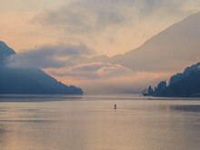 Dawn At White Lake In Austrian South Alps...In The Distance A Person Who Is Stand Up Paddling Can Be Seen.
