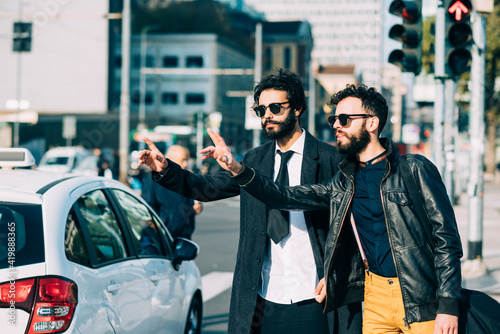 Obraz na plátne Two young caucasian bearded businesslike men outdoor calling a cab