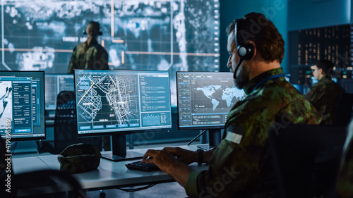 Military Surveillance Officer Working on a City Tracking Operation in a Central Office Hub for Cyber Control and Monitoring for Managing National Security, Technology and Army Communications Fotobehang