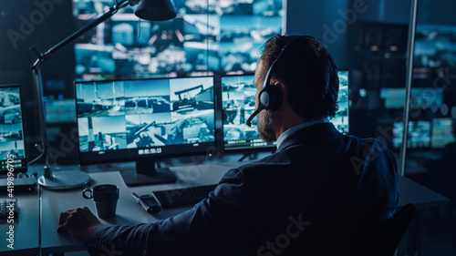 Billede på lærred Male Officer Works on a Computer with Surveillance CCTV Video in a Harbour Monitoring Center with Multiple Cameras on a Big Digital Screen