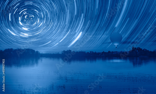 Long exposure photo of night sky star trail over the  lake at sunset Fototapet