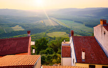 Motovun Croatia. View With High Hill At Green Lowland. Red Tegular Roof With Chimney. Picturesque Landscape. Sunset Over Forest And Background.