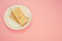 Plate With Salty Crackers On A Pink Surface