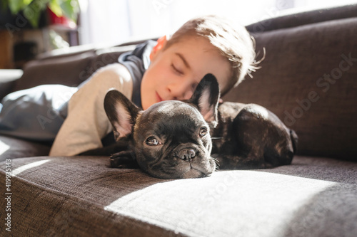 Tablou Canvas Young Boy with French Bulldog Puppy on the sofa