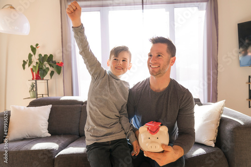 Stampa su Tela Father with little son with piggy bank at home