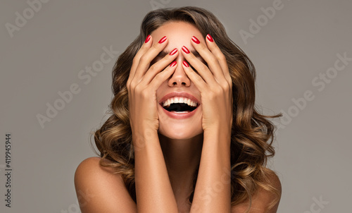 Beautiful woman with curly hair and red nails manicure . Girl happy  laughs  closes her face with a hand .