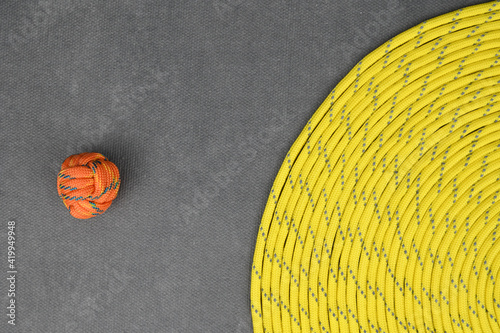 Obraz Yellow paracord, coiled in a tight spiral. To the left lies a tight knot tied with orange paracord. - fototapety do salonu