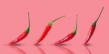 Small Hot Red Chilli Peppers Arranged In A Row On A Pink Background