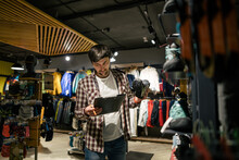 Sporting Goods Store Owner With Clipboard Checking Inventory. Tourist Store Manager Working Near Showcase With Hiking Boots Makes Check List Of Orders. Salesman Exhibit Display Of Walking Boots
