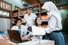 A Female Student In A Headscarf Holding A Book And Giving An Explanation As Four High School Students Study Together Using A Laptop
