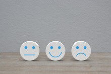 Neutral, Happy Smiley, Negative Face Emoticon On White Circle Shape On Wooden Table Over White Wall Background, Business Customer Service Evaluation And Feedback Rating Concept