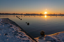 A Beautiful Sunset Seen From A Snowy Boat Dock Where A Line With Buoys Runs To An Island With Resting Cormorants In Lake Zoetermeerse Plas