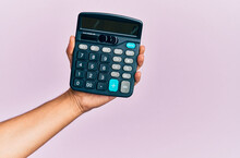 Hand Of Young Hispanic Man Holding Calculator Over Isolated Pink Background.