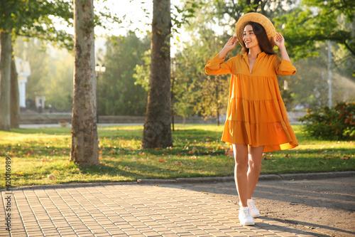 Fotografia Beautiful young woman wearing stylish yellow dress and straw hat in park