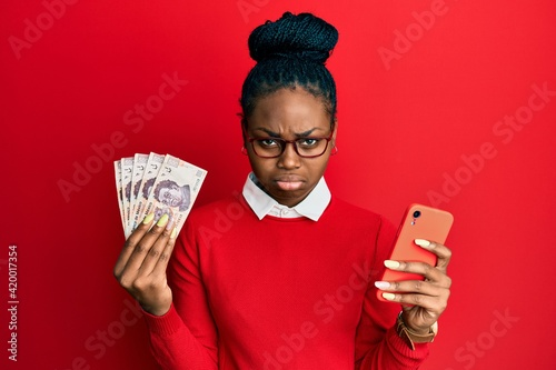 Young african american woman using smartphone holding mexican peso banknotes depressed and worry for distress, crying angry and afraid Fototapet