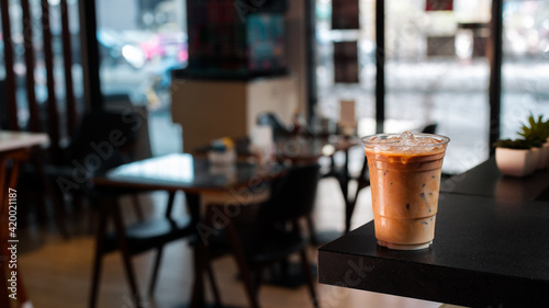 Fototapeta Close-up glass of iced coffee with milk on the table obraz