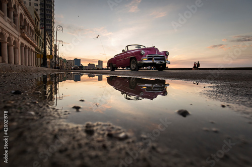 Tablou Canvas Old car on Malecon street of Havana with colourful sunset in background