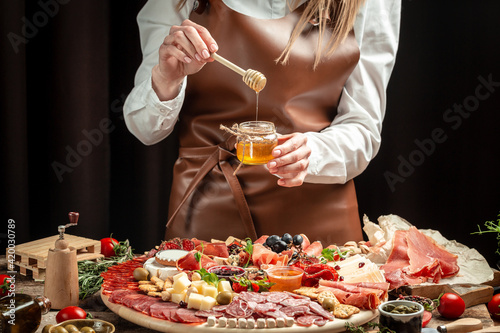 Slika na platnu Women's hands holding honey, Antipasto platter
