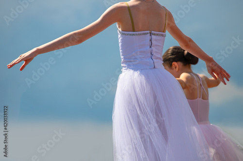 Foto Little ballerinas dancing against the Cloudy sky