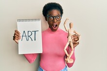 Young African American Girl Holding Wooden Manikin And Art Word On Notebook Celebrating Crazy And Amazed For Success With Open Eyes Screaming Excited.