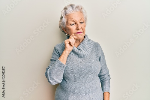 Obraz Senior grey-haired woman wearing casual clothes thinking concentrated about doubt with finger on chin and looking up wondering - fototapety do salonu