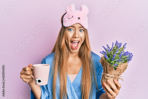 Beautiful young blonde woman wearing pajama drinking a cup of infused lavender celebrating crazy and amazed for success with open eyes screaming excited.
