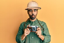 Young Hispanic Man Wearing Explorer Hat And Vintage Camera Making Fish Face With Mouth And Squinting Eyes, Crazy And Comical.
