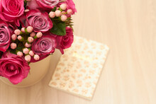 Top Of View To Red And Pink Roses Bouquet On Light Brown Table With Notebook. Copy Space.