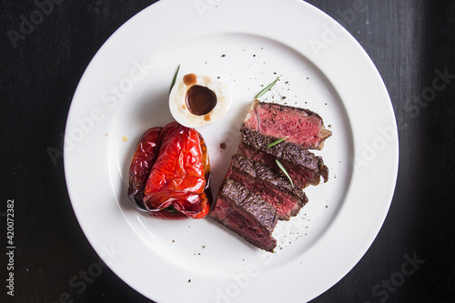 Fototapeta chopped steak served on a plate with baked pepper and sauce obraz
