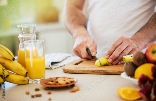 Fotografia Handsome young sporty smiling man in the kitchen is preparing vegan healthy frui