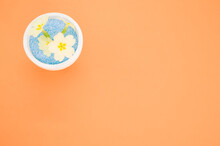 Overhead Shot Of Yellow Flowers In A Pot Of Blue Sand On An Orange Background
