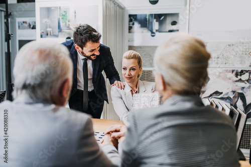 Fototapeta Senior couple are buying ceramic tiles and utensils for their home while salesman and saleswoman are helping them to make right decision. obraz