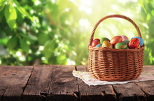 Wicker Basket With Easter Colorful Eggs On Rustic Wooden Table With Defocused Lush Foliage At Background. Backdrop For Product Display On Top Of The Table. Spring Easter Composition With Copy Space.