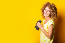 Cheerful Smiling Curly Young Woman Holding Binoculars On Yellow Background.