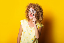 Smiling Curly Young Woman Looking Through A Magnifying Glass On A Yellow Background.