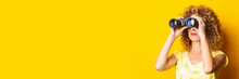 Curly Young Woman Looks Through Binoculars On A Yellow Background. Banner.