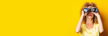 Curly-haired Girl Looks Through Binoculars On A Bright Yellow Background. Banner.
