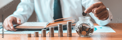 Obraz na plátně Financial businessman with coins put in a jar, Saving money for future growth and knowing how to manage your spending wisely, Saving money for business growth or long-term profitability