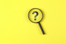 Business And Financial Concept With Magnifying Glass, Question Mark On Yellow Background Flat Lay.