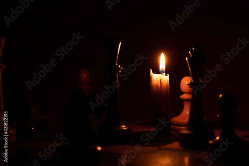 chess pieces stand on a chessboard and next to a burning candle in the dark, pla Fototapet