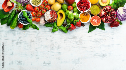 Vegan food banner. Fresh vegetables and fruits and berries on a white wooden background. Free space for your text.