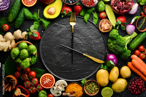 Fototapeta The concept of dietary nutrition: fresh vegetables and fruits. Cutlery and a plate in the form of a clock. Top view. Free space for your text. obraz