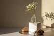 Leinwandbild Motiv minimalism still life with a branch of a gypsophila flower standing on a white paper cube and stones