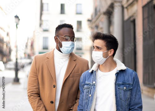 Two friends with face mask talking and walking. Afro-american and caucasian man.