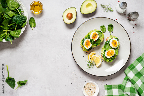 Fototapeta Healthy toast with sliced avocado, boiled eggs, spices and fresh spinach. Delicious breakfast or snack on gray stone background. top view, space for text obraz