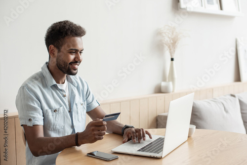 Young man holding credit card and using laptop at home, Businessman or entrepreneur working, Online shopping, e-commerce, internet banking, spending money, working from home concept