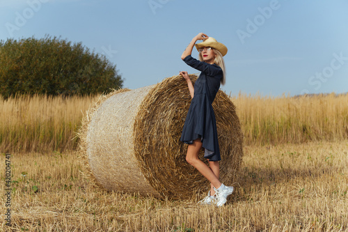 Slika na platnu Beautiful girl villager posing in a dress near a bale of hay in a field