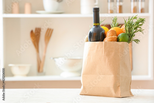 Fototapeta Paper bag with different products on table in kitchen obraz