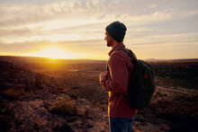 Happy Tourist Man With Backpack Standing On Top Mountain Looking Into The Distance At Morning Sunrise