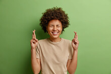 Cheerful Beautiful Curly Haired Ethnic Young Woman Crosses Fingers Waits Announcement Of Results Hopes Dreams Come True Smiles Broadly Dressed In Casual T Shirt Isolated Over Green Background
